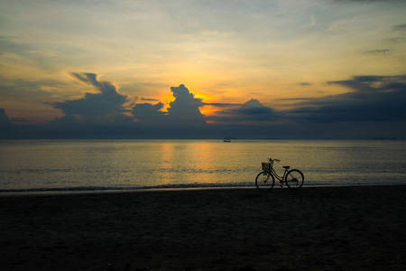 Beautiful golden sunrise by the beach with bicycle on the foreground and fishing boat on the horizon