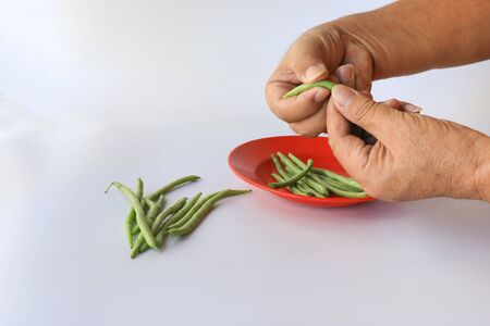 Hands snapping green beans (Phaseolus Vulgaris) into a red plate isolated on white, group of green beans