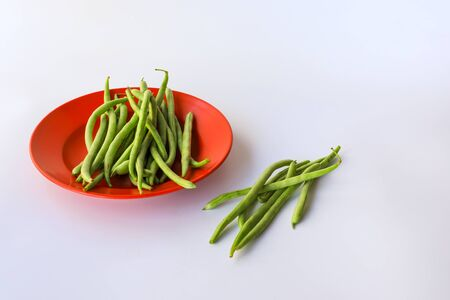 Snap beans (Phaseolus Vulgaris) in a red plate isolated on white, group of green beans