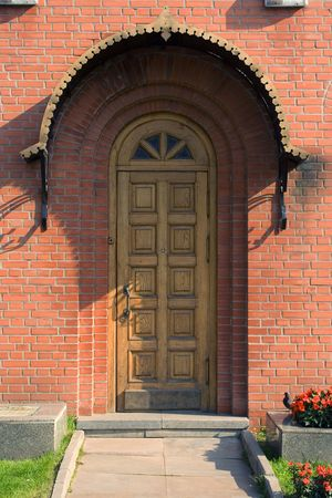 socle: Old wooden door with metal moulding in a red brick wall
