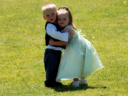 A portrait of twin boy and girl hugging in the great outdoors
