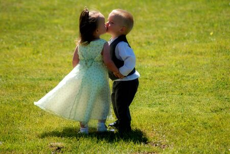 A portrait of twin boy and girl stealing a kiss outdoors