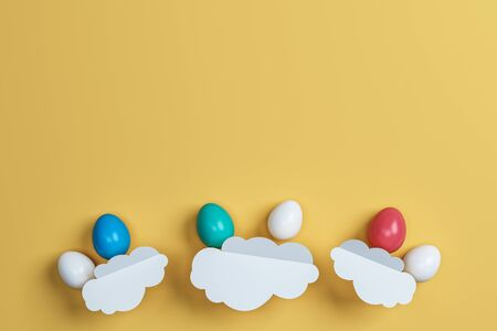 colorful Easter eggs and cloud on yellow background. Space for text. Minimal concept. Abstract idea. Flat lay. Top view. 3d rendering.