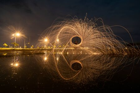 Burning of steel wool reflection in water. Banco de Imagens - 143081522