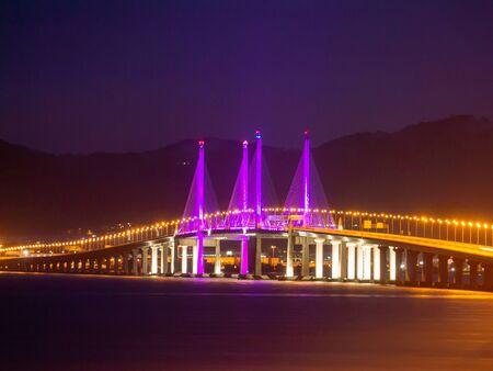 Penang Second Bridge with purple lighting in dawn hour.