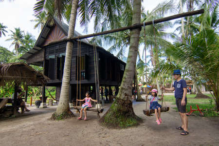 Penaga, PenangMalaysia - Oct 27 2019: Children play swings in front of wooden Malays hut