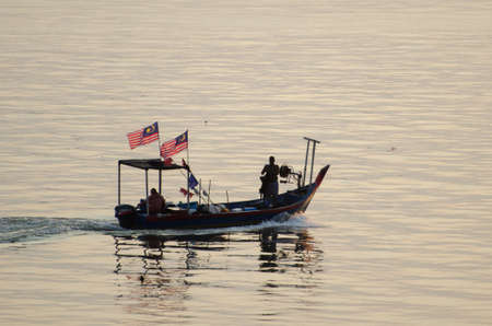 Batu Maung, Penang/Malaysia - Aug 31 2020: Fisherman on the journey go to sea. Malaysia flag is hang on boat.