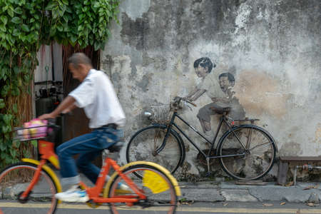 Georgetown, Penang/Malaysia - Sep 25 2020: A man cycling pass the mural art Little children on a bicycle Editorial