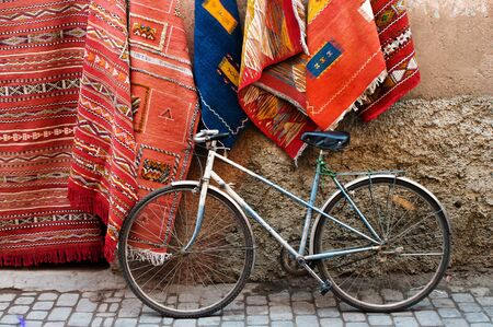 old bicycle: Old bicycle and traditional carpets on the street of Marrakesh, Morocco