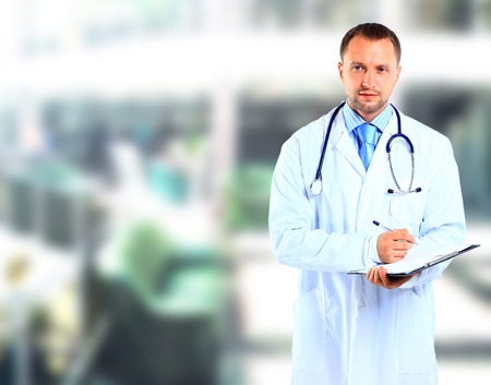 doctor's office: portrait of doctor in white coat and stethoscope with arms crossed  Stock Photo