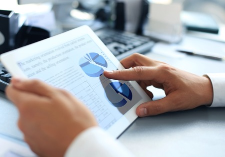business solutions: Business person analyzing financial statistics displayed on the tablet screen