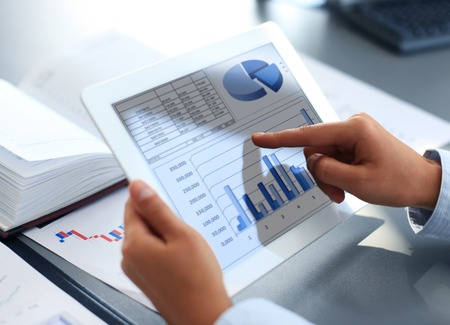 business results: Business person analyzing financial statistics displayed on the tablet screen