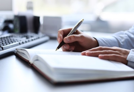 writing pad: businessman writes in a notebook while sitting at a desk Stock Photo