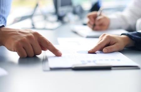 reunion de trabajo: Persona de negocios irreconocible análisis de gráficos y tomar notas