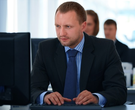 businessman working at his computer: Portrait of a smiling young businessman working on computer at office with his colleagues  Stock Photo