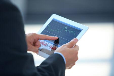 financial market: Businessman holding digital tablet