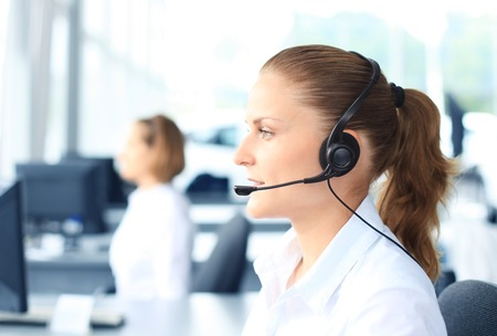 call center office: Beautiful young female call center operator with headset in office