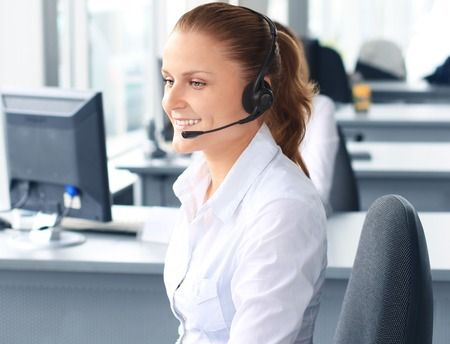 Beautiful young female call center operator with headset in office