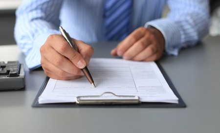 document management: Businessman sitting at office desk signing a contract
