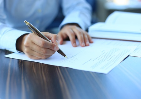 subscribing: Businesswoman sitting at office desk signing a contract with shallow focus on signature