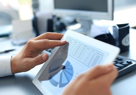 estadisticas: Persona de negocios an�lisis de las estad�sticas financieras muestra en la pantalla de la tableta