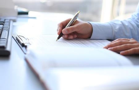 hombre escribiendo: Manos de la empresaria que señala en el documento de negocios Foto de archivo