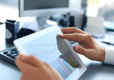 Persona di affari analisi statistiche finanziarie visualizzato sullo schermo del tablet