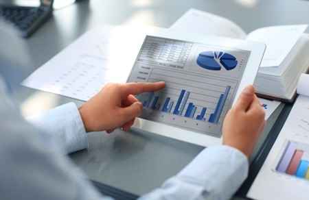 Business person analyzing financial statistics displayed on the tablet screen Imagens - 30674370
