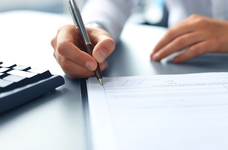 legal office: Businesswoman sitting at office desk signing a contract with shallow focus on signature