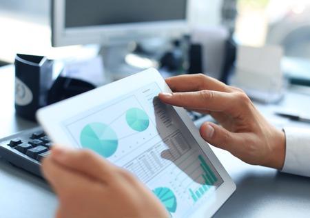 tecnologia: Persona di affari analisi statistiche finanziarie visualizzato sullo schermo del tablet