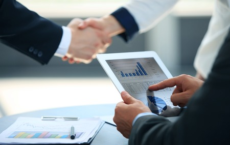 people office: Business associates shaking hands in office Stock Photo