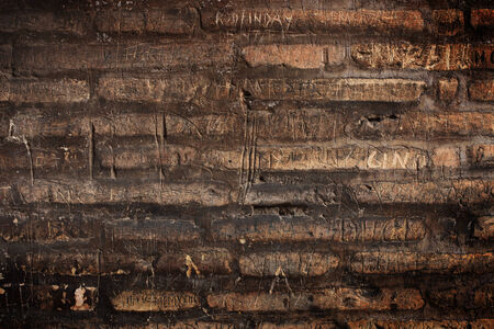 inscriptions: The historical brick wall with engraved inscriptions