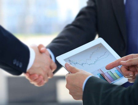 businessmen shaking hands: Business associates shaking hands in office