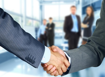 hand job: Business associates shaking hands in office