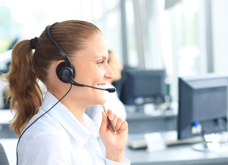 Beautiful young female call center operator with headset in office  photo
