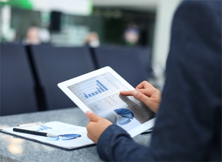 graphics tablet: Business person analyzing financial statistics displayed on the tablet screen