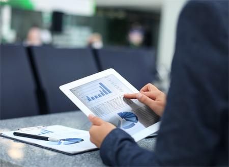 personne d'affaires l'analyse des statistiques financières affiché sur l'écran de la tablette