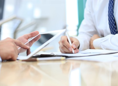 Image of two young businessmen using touchpad at meeting Stock Photo