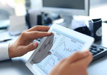 statistical: Business person analyzing financial statistics displayed on the tablet screen
