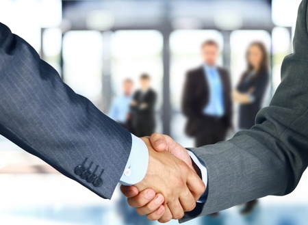 businessmen shaking hands: Business associates shaking hands in office Stock Photo
