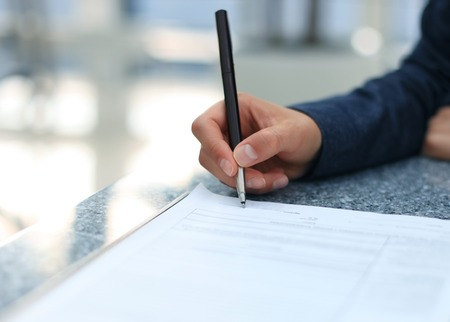 Businesswoman sitting at office desk signing a contract with shallow focus on signature photo