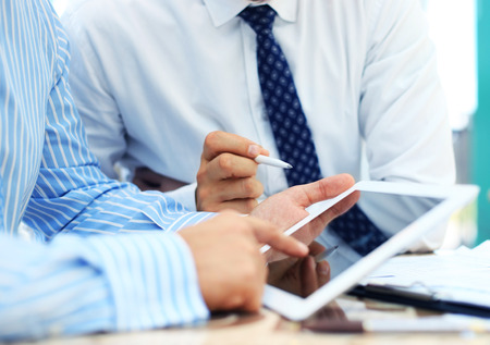 financial team: Image of human hand pointing at touchscreen in working environment at meeting