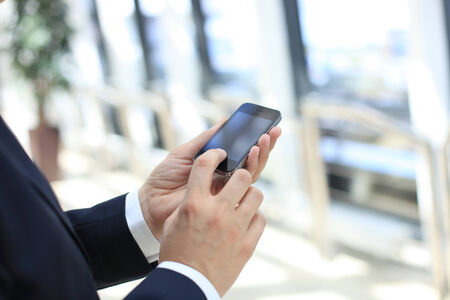 Close up of a business man using mobile smart phone photo