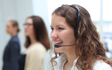 phone conversation: Young employee working with a headset and accompanied by her team Stock Photo