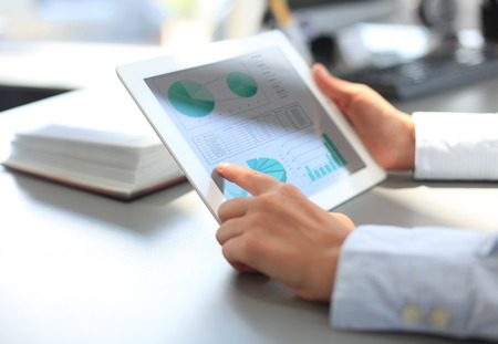 Business graph: Business person analyzing financial statistics displayed on the tablet screen