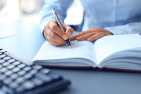 businessman writes in a notebook while sitting at a desk Foto de archivo