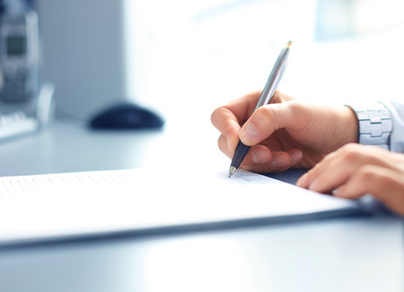 hand holding pen: Close-up of Businesswoman makes a note at business document