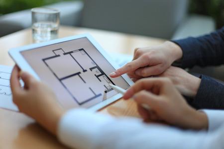 不動産業者の電子タブレット上の家の計画を示す 写真素材