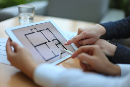 Real-estate agent showing house plans on electronic tablet Foto de archivo