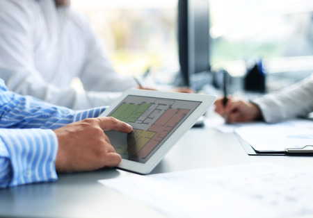 Real-estate agent showing house plans on electronic tablet Standard-Bild